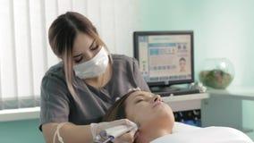 El cliente femenino bonito joven se está enfriando en la cámara lenta del procedimiento facial hidráulico del vacío metrajes