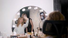 El cliente femenino de la tienda de belleza está tomando el selfie con el artista de maquillaje profesional delante del espejo co metrajes