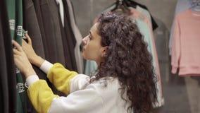 El cliente femenino está viendo las camisetas con los modelos en tienda de la ropa metrajes