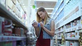 El cliente femenino joven está tomando el tarro dos con la pintura en una tienda para los constructores almacen de video