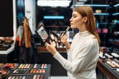 El cliente femenino mira el espejo en tienda del maquillaje fotografía de archivo libre de regalías