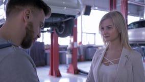 El cliente femenino sacude las manos con el representante/delegado técnico de reparación auto y da llaves del coche en el fondo d almacen de video