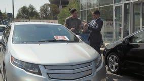 El cliente firma el acuerdo del coche de compra en concesión de coche metrajes