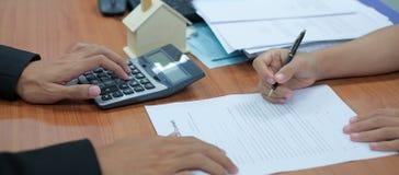 el cliente firma el contrato de préstamo hipotecario con el agente inmobiliario imagenes de archivo