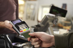 El cliente hace el pago con tarjeta de crédito sobre contador en un café foto de archivo