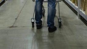 El cliente masculino con el carro de la compra camina en la tienda almacen de video