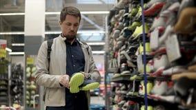 El cliente masculino está tomando los zapatos del deporte del estante en un hipermercado del deporte almacen de metraje de vídeo