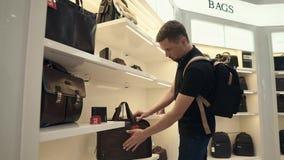El cliente masculino joven está examinando los bolsos en una tienda, mercancías está en los estantes metrajes