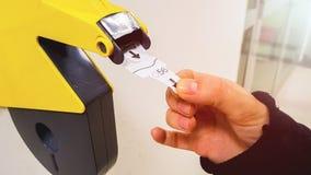 El cliente saca con la mano de un boleto numerado la máquina amarilla del dispensador del número, esperar en línea de servicio y  imágenes de archivo libres de regalías