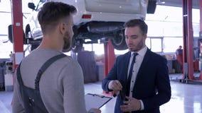 El cliente sacude las manos con el servicio de reparación auto represantative y da llaves del coche en el fondo del vehículo en a almacen de video
