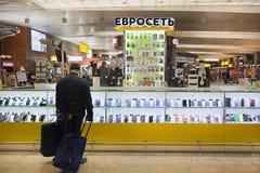 El cliente se está colocando en el fron de la ventana en la tienda de Evroset en Moscú en el aeropuerto Foto de archivo libre de regalías