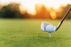 El club de golf detrás de la pelota de golf en el soporte Contra la perspectiva de hierba y de puesta del sol Imagenes de archivo
