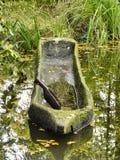 El cobertizo de la piragua construido de un solo tronco flota en la orilla de una corriente en el bosque imagen de archivo