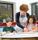 El cocer al horno de la abuela y de los grandchilds Fotografía de archivo