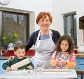 El cocer al horno de la abuela y de los grandchilds Imagen de archivo libre de regalías