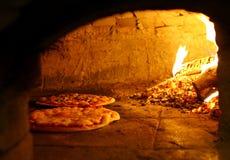 El cocer al horno de las pizzas Imágenes de archivo libres de regalías