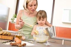 El cocer al horno - mujer con el niño que prepara la pasta Fotos de archivo libres de regalías