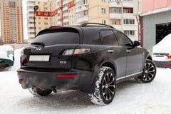 El coche adaptado costoso negro Infiniti Fx 35 en el viejo cuerpo se coloca con el motor dio vuelta encendido en el invierno cont fotos de archivo libres de regalías