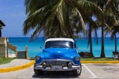 El coche azul americano de la obra clásica de Buick ocho parqueó debajo de las palmas en la playa en Varadero Cuba - el reportaje foto de archivo libre de regalías