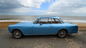 El coche azul cl?sico de Alvis Motor parque? en la 'promenade' de la orilla del mar foto de archivo