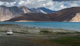El coche blanco en el lago Pangong con la opinión de la belleza rodeado por la cordillera y la turquesa colorean el lago Fotos de archivo libres de regalías