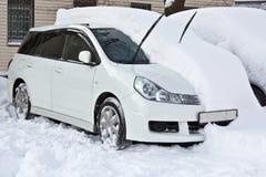 El coche blanco está bajo la nieve Foto de archivo