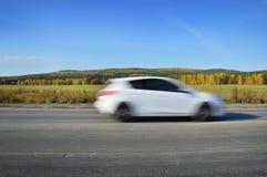 El coche blanco monta en el camino en la velocidad Imágenes de archivo libres de regalías