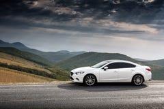 El coche blanco parqueó en la carretera de asfalto del campo cerca de las montañas verdes Foto de archivo