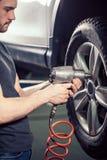 El coche cambiante del mecánico rueda adentro el garaje de la reparación auto Foto de archivo