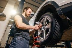 El coche cambiante del mecánico rueda adentro el garaje de la reparación auto Fotografía de archivo