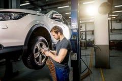 El coche cambiante del mecánico rueda adentro el garaje de la reparación auto Imágenes de archivo libres de regalías