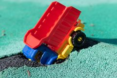 El coche cayó en el hoyo El camión plástico del juguete con un cuerpo rojo tenía un accidente Agujero en Asphalt Coating El c fotos de archivo libres de regalías