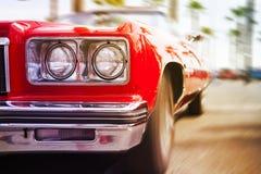 El coche clásico rojo se divierte entrar rápidamente, en fondo de la falta de definición de movimiento Imagen de archivo libre de regalías