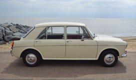 El coche color nata clásico 1100 de motor de Austin MG parqueó en la 'promenade' de la orilla del mar imagen de archivo