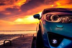 El coche compacto azul de SUV con deporte y diseño moderno parqueó en el camino concreto por el mar en la puesta del sol Respetuo Imagen de archivo libre de regalías