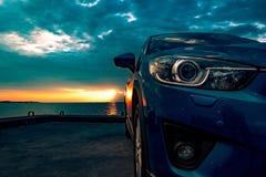 El coche compacto azul de SUV con deporte y diseño moderno parqueó en el camino concreto por el mar en la puesta del sol Technolo Fotos de archivo libres de regalías