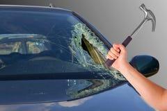 El coche con el vidrio quebrado y el sostenerse femenino martillan Imagenes de archivo
