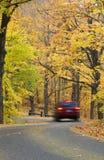El coche conduce abajo del camino endoselado del otoño Fotos de archivo