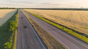 El coche conduce a lo largo de la carretera colorida entre los campos de trigo en la puesta del sol, el coche monta a lo largo de almacen de metraje de vídeo