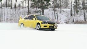El coche conduce por la pista helada en el lago nevado en el invierno El competir con de coche deportivo en circuito de carreras  almacen de video