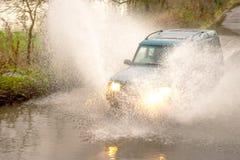 el coche 4x4 conduce a través de las aguas de inundación en carril del país imagenes de archivo