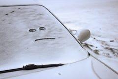 El coche cubrió con nieve con una cara malvada sobre el vidrio Paisaje del invierno imagenes de archivo