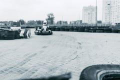 El coche de competición del kart en la pista, campeonato, deportes activos, diversión extrema, el conductor guarda sus manos en l fotografía de archivo libre de regalías