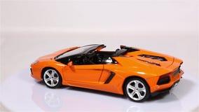 El coche de deportes anaranjado del modelo de escala del automóvil descubierto de Lamborghini Aventador LP 700-4 es rotación aisl almacen de metraje de vídeo