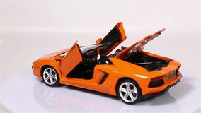El coche de deportes anaranjado del modelo de escala del automóvil descubierto de Lamborghini Aventador LP 700-4 es rotación aisl metrajes