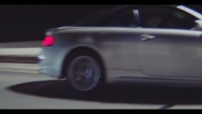 El coche de deportes cercano conduce a lo largo de la calle más allá de luces por la tarde almacen de metraje de vídeo