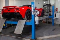 El coche de deportes rojo aumentó en una elevación en un taller de reparaciones, un parachoques trasero y un alerón del coche fotos de archivo