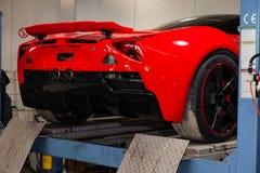 El coche de deportes rojo aumentó en una elevación en un taller de reparaciones, un parachoques trasero y un alerón del coche fotografía de archivo libre de regalías