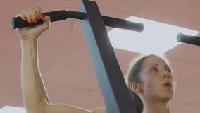 El coche de la aptitud del club de deportes hace tirón-UPS en el simulador para consolidar los músculos del hombro Una mujer hace almacen de video