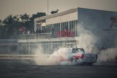 El coche de la recogida realiza el neumático de la quemadura en la pista Foto de archivo libre de regalías